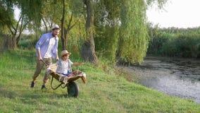 Εύθυμος ανόητος μπαμπάδων γύρω με το μικρό γιο του wheelbarrow στις οικογενειακές διακοπές σε αγροτικό φιλμ μικρού μήκους