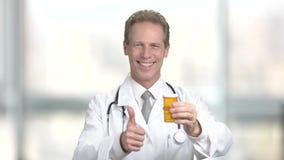 Εύθυμος αρσενικός γιατρός με τα χάπια, θολωμένο υπόβαθρο φιλμ μικρού μήκους