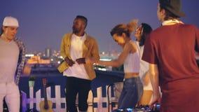 Εύθυμος αρσενικός deejay λειτουργεί με τη μίξη της κονσόλας και το χορό ενώ ομάδα φίλων καυκάσιων και αφροαμερικάνου απόθεμα βίντεο