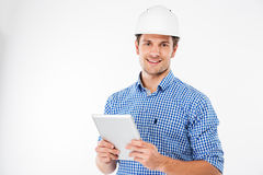 Εύθυμος αρχιτέκτονας ατόμων στο σκληρό καπέλο που στέκεται και που χρησιμοποιεί την ταμπλέτα Στοκ Εικόνα