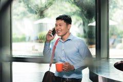 Εύθυμος ασιατικός νεαρός άνδρας που μιλά στο κινητό τηλέφωνο κρατώντας ένα φλιτζάνι του καφέ Στοκ εικόνες με δικαίωμα ελεύθερης χρήσης