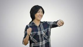 Εύθυμος ασιατικός χορός κοριτσιών διασκέδασης που εξετάζει τη κάμερα στο άσπρο υπόβαθρο φιλμ μικρού μήκους