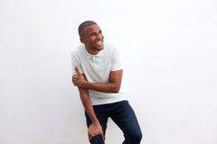 Εύθυμος αφρικανικός τύπος που κλίνει στον τοίχο που κοιτάζει μακριά και που χαμογελά Στοκ φωτογραφίες με δικαίωμα ελεύθερης χρήσης