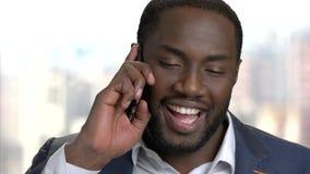 Εύθυμος αφροαμερικανός επιχειρηματίας που μιλά στο τηλέφωνο απόθεμα βίντεο