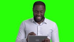 Εύθυμος αφροαμερικανός τύπος που χρησιμοποιεί την ταμπλέτα υπολογιστών φιλμ μικρού μήκους