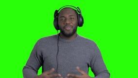 Εύθυμος αφροαμερικανός τύπος στα ακουστικά απόθεμα βίντεο
