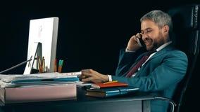 Εύθυμος γενειοφόρος επιχειρηματίας που εργάζεται στον υπολογιστή του και που μιλά στο τηλέφωνο κυττάρων Στοκ Εικόνες