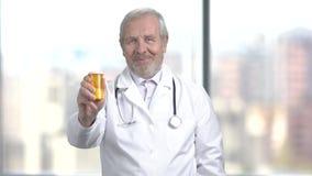 Εύθυμος γιατρός με τα χάπια, θολωμένο υπόβαθρο απόθεμα βίντεο