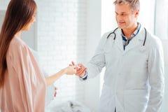 Εύθυμος γιατρός που δίνει το θερμόμετρο στη έγκυο γυναίκα Στοκ Εικόνα