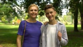 Εύθυμος γιος και mom αγκάλιασμα να παρουσιάσει αντίχειρας-επάνω, χόμπι ευχαρίστησης από κοινού απόθεμα βίντεο