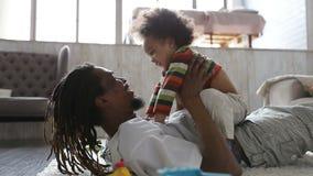 Εύθυμος γιος πατέρων και μικρών παιδιών που έχει τη διασκέδαση στο σπίτι απόθεμα βίντεο