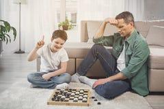 Εύθυμος γιος που κερδίζει τον πατέρα του στο διανοητικό παιχνίδι Στοκ φωτογραφίες με δικαίωμα ελεύθερης χρήσης