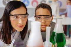 Εύθυμος δάσκαλος και ο σπουδαστής της που παρατηρούν τη χημική αντίδραση Στοκ Εικόνες