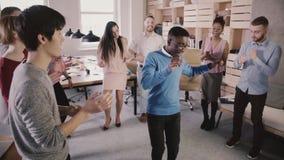 Εύθυμος διευθυντής αφροαμερικάνων που χορεύει στον κύκλο με τους συναδέλφους στο περιστασιακό κόμμα εορτασμού γραφείων διασκέδαση φιλμ μικρού μήκους