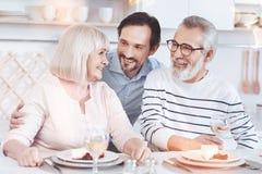 Εύθυμος ενήλικος γιος που αγκαλιάζει τους θετικούς ηλικιωμένους γονείς του στοκ εικόνες