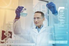 Εύθυμος επιστήμονας που χαμογελά και που βάζει ένα μπουκάλι με το μπλε υγρό επάνω Στοκ φωτογραφία με δικαίωμα ελεύθερης χρήσης