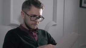 Εύθυμος επιχειρηματίας με τα γυαλιά στο γραφείο που λαμβάνει τις ειδήσεις, κρατά ένα έγγραφο συμβάσεων απόθεμα βίντεο