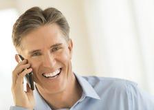 Εύθυμος επιχειρηματίας που απαντά στο έξυπνο τηλέφωνο Στοκ εικόνες με δικαίωμα ελεύθερης χρήσης