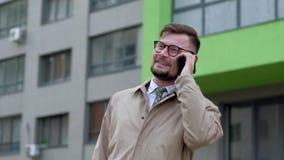 Εύθυμος επιχειρηματίας που μιλά στο τηλέφωνό του υπαίθρια απόθεμα βίντεο