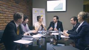 Εύθυμος επιχειρηματίας που μιλά με τους συναδέλφους στην αίθουσα συνεδριάσεων απόθεμα βίντεο