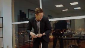 Εύθυμος επιχειρηματίας που συλλέγει τα μετρητά χρημάτων από τον υπολογιστή γραφείου στο γραφείο βραδιού απόθεμα βίντεο