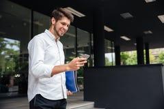 Εύθυμος επιχειρηματίας που χρησιμοποιεί το smartphone στην πόλη Στοκ Εικόνες