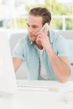 Εύθυμος επιχειρηματίας στο τηλέφωνο χρησιμοποιώντας τον υπολογιστή Στοκ εικόνα με δικαίωμα ελεύθερης χρήσης