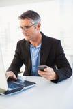 Εύθυμος επιχειρηματίας χρησιμοποιώντας το lap-top και κρατώντας το smartphone Στοκ φωτογραφία με δικαίωμα ελεύθερης χρήσης