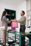 Εύθυμος εργαζόμενος καταστημάτων που δίνει τις τσάντες αγορών σε έναν πελάτη στοκ εικόνες
