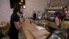 Εύθυμος ευτυχής θηλυκός πωλητής που εξυπηρετεί έναν πελάτη με έναν καφέ για να πάει και ποιος αστειεύεται με την κατά τον πληρωμή απόθεμα βίντεο