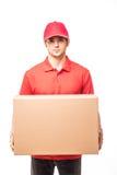 Εύθυμος ευτυχής νέος αγγελιαφόρος ατόμων παράδοσης που κρατά ένα κουτί από χαρτόνι και που χαμογελά στεμένος στο άσπρο υπόβαθρο Στοκ Φωτογραφίες