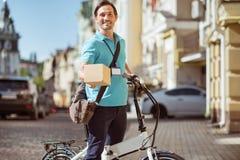 Εύθυμος ευχαριστημένος αγγελιαφόρος που κρατά ένα κιβώτιο στοκ φωτογραφίες με δικαίωμα ελεύθερης χρήσης