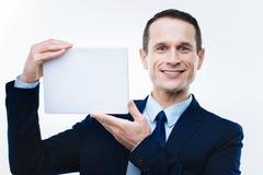 Εύθυμος ευχαριστημένος επιχειρηματίας που χρησιμοποιεί μια σύγχρονη συσκευή στοκ φωτογραφίες