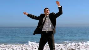 Εύθυμος ελεύθερος επιχειρηματίας που χορεύει στην παραλία απόθεμα βίντεο