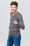 Εύθυμος ελκυστικός νεαρός άνδρας που χαμογελά και που δείχνει σε σας Στοκ Εικόνες