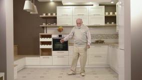 Εύθυμος ηληκιωμένος που χορεύει στην κουζίνα απόθεμα βίντεο