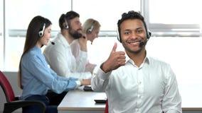 Εύθυμος ινδικός εργαζόμενος τηλεφωνικών κέντρων που παρουσιάζει αντίχειρα φιλμ μικρού μήκους