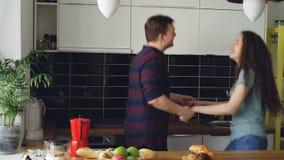 Εύθυμος και ελκυστικός νέος ερωτευμένος χορεύοντας μαζί φοβιτσιάρης χορός ζευγών στην κουζίνα στο σπίτι στις διακοπές απόθεμα βίντεο
