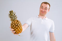 Εύθυμος και συναισθηματικός τύπος που κρατά έναν ανανά στο χέρι του σε ένα άσπρο υπόβαθρο Στοκ Εικόνες