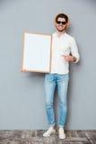 Εύθυμος κενός λευκός πίνακας εκμετάλλευσης ατόμων και υπόδειξη σε το Στοκ εικόνες με δικαίωμα ελεύθερης χρήσης
