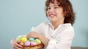 Εύθυμος μαθητής με ένα καλάθι των αυγών Πάσχας Το σγουρός-μαλλιαρό αγόρι γελά διασκέδαση φιλμ μικρού μήκους
