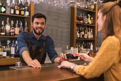 Εύθυμος μπάρμαν που χαμογελά ενώ ο πελάτης του που πληρώνει το λογαριασμό στοκ εικόνα