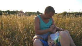 Εύθυμος μπαμπάς και το παιδί του που έχουν τη διασκέδαση μαζί σε ένα πάρκο Πατέρας που ο μικρός γιος του υπαίθριος ευτυχείς νεολα φιλμ μικρού μήκους