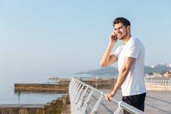 Εύθυμος νέος αθλητικός τύπος που μιλά στο κινητό τηλέφωνο υπαίθρια Στοκ φωτογραφία με δικαίωμα ελεύθερης χρήσης