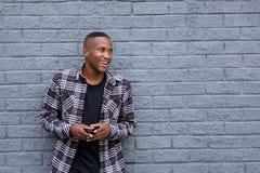 Εύθυμος νέος αφρικανικός τύπος με ένα τηλέφωνο κυττάρων που κοιτάζει μακριά και sm Στοκ Εικόνα