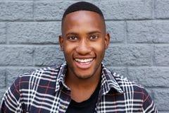 Εύθυμος νέος αφρικανικός τύπος που χαμογελά ενάντια στον γκρίζο τοίχο Στοκ Εικόνα