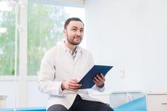 Εύθυμος νέος γιατρός που κρατά μια περιοχή αποκομμάτων και που με το χέρι του στο θάλαμο νοσοκομείων Στοκ φωτογραφίες με δικαίωμα ελεύθερης χρήσης