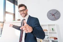 εύθυμος νέος επιχειρηματίας που δείχνει με το δάχτυλο και το χαμόγελο Στοκ Εικόνα