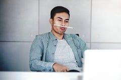 Εύθυμος νέος επιχειρηματίας που εργάζεται στο lap-top υπολογιστών στην αρχή στοκ εικόνες με δικαίωμα ελεύθερης χρήσης