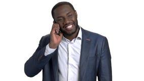 Εύθυμος νέος μαύρος επιχειρηματίας που μιλά στο τηλέφωνο κυττάρων απόθεμα βίντεο